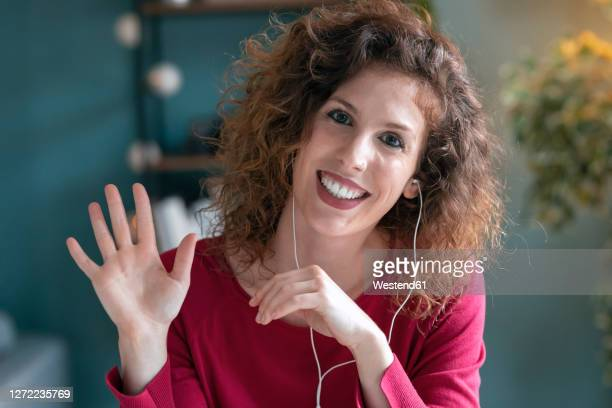 smiling businesswoman wearing headphones while waving at home - waving gesture stock pictures, royalty-free photos & images