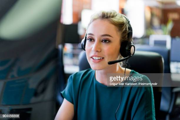 smiling businesswoman wearing headset at office - customer relationship management stock photos and pictures