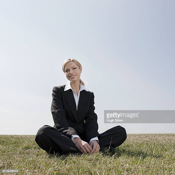 smiling businesswoman wearing suit, while sitting outdoors in the sunshine - hugh sitton stock pictures, royalty-free photos & images