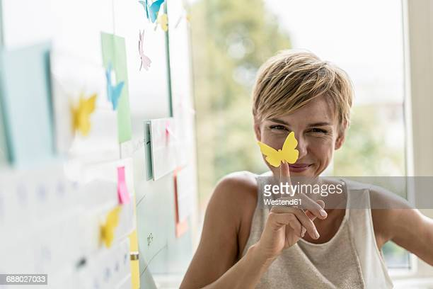 Smiling businesswoman with adhesive notes at whiteboard in modern office