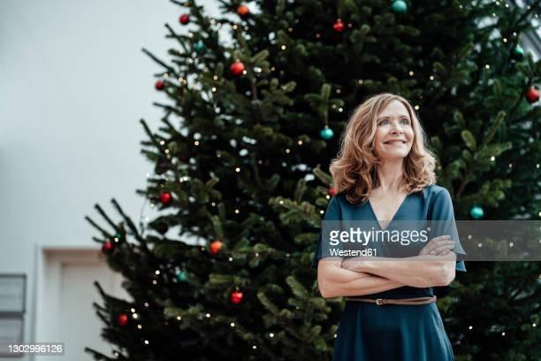 smiling businesswoman with arms crossed looking away against christmas tree in office - goed gekleed stockfoto's en -beelden