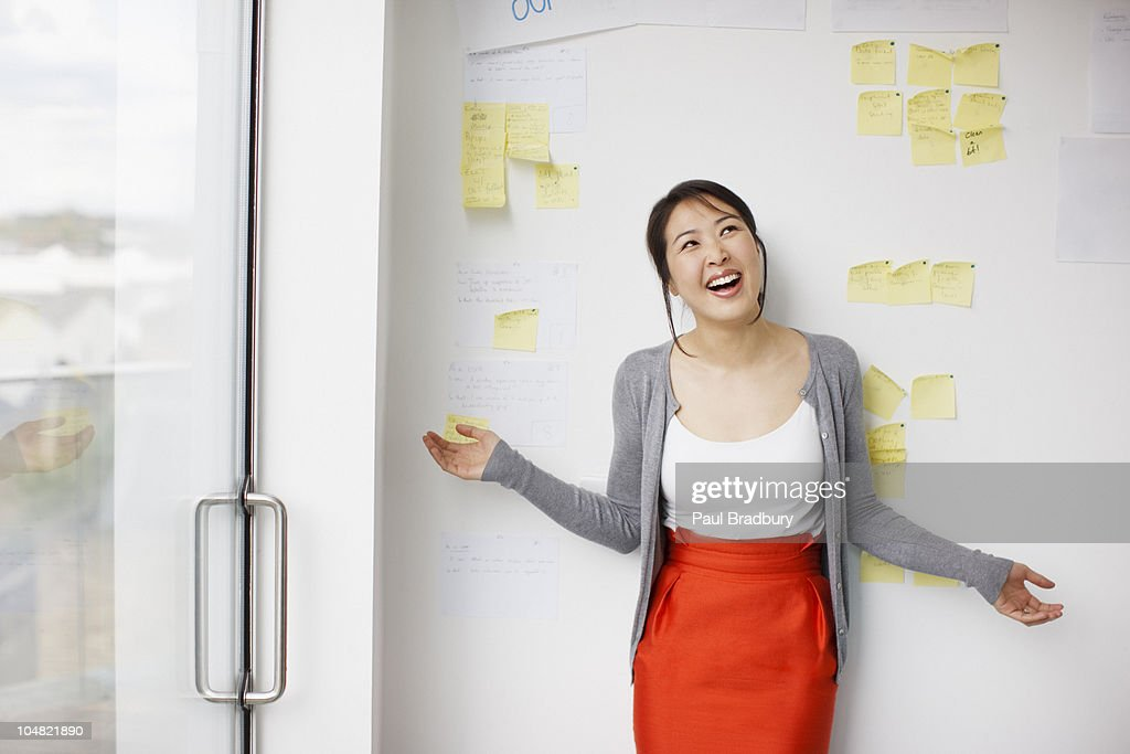 Smiling businesswoman with arms outstretched in front of whiteboard with adhesive notes : Stock Photo