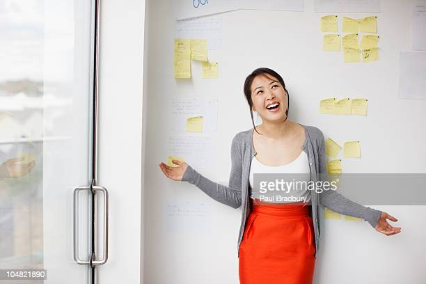 smiling businesswoman with arms outstretched in front of whiteboard with adhesive notes - arms outstretched stock pictures, royalty-free photos & images