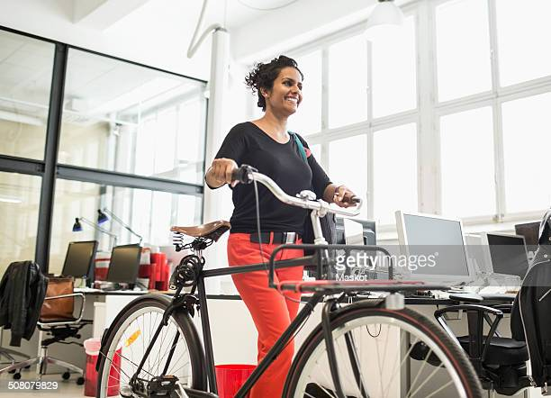 Smiling businesswoman with bicycle walking in creative office
