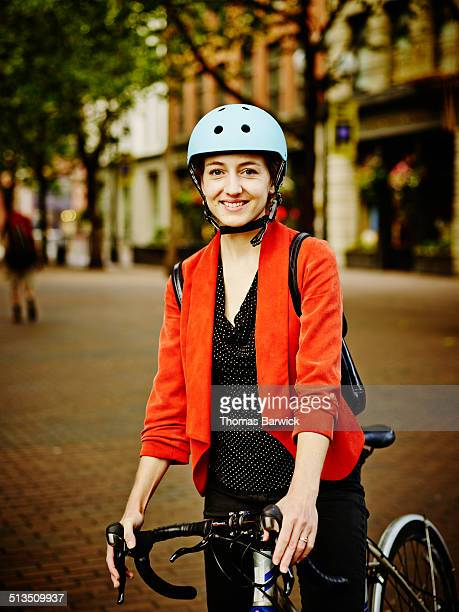 smiling businesswoman with bike on sidewalk - cycling helmet stock pictures, royalty-free photos & images