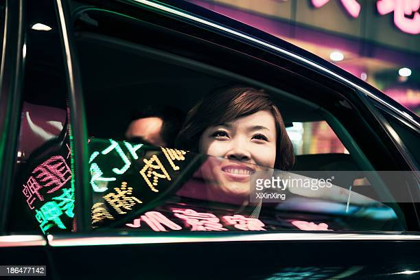 Smiling businesswoman with car window rolled down looking out at the nightlife in Beijing