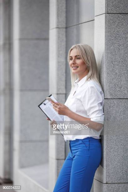 Smiling businesswoman with clipboard and cell phone leaning against a wall