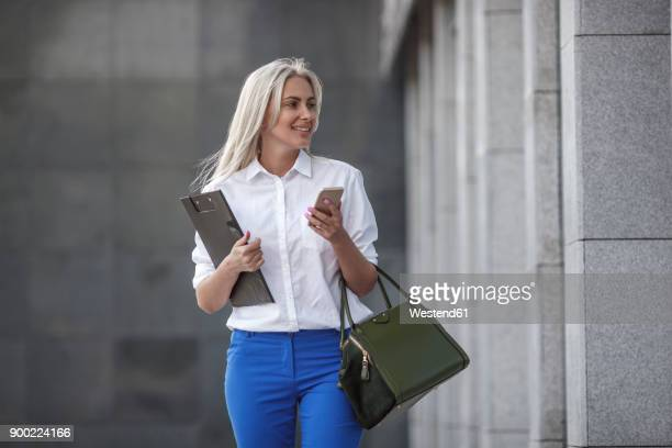 Smiling businesswoman with clipboard, handbag and cell phone on the move