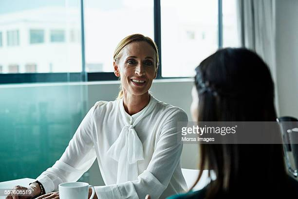smiling businesswoman with colleague at desk - blouse stock pictures, royalty-free photos & images
