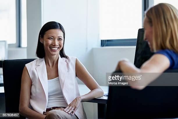 smiling businesswoman with colleague in office - waistcoat - fotografias e filmes do acervo