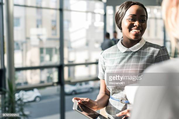 Smiling businesswoman with colleague on office floor