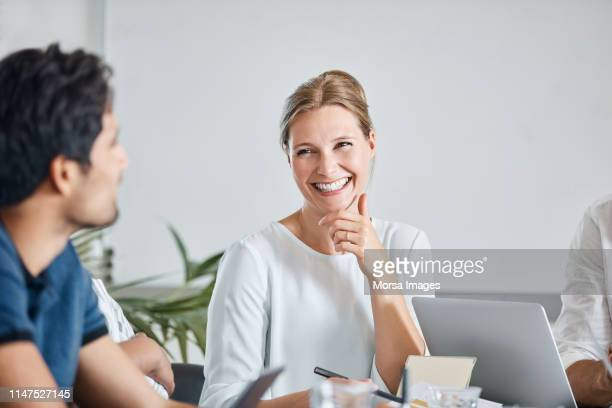 smiling businesswoman with coworkers in meeting - scandinavia stock pictures, royalty-free photos & images