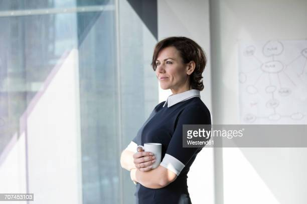 Smiling businesswoman with cup of coffee looking out of window