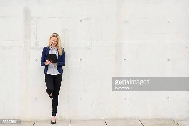 Smiling businesswoman with digital tablet leaning on concrete wall