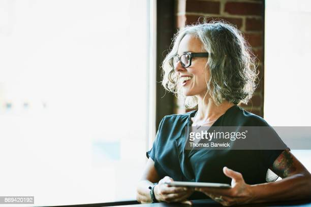 smiling businesswoman with digital tablet listening during meeting in office - gray hair stock photos and pictures