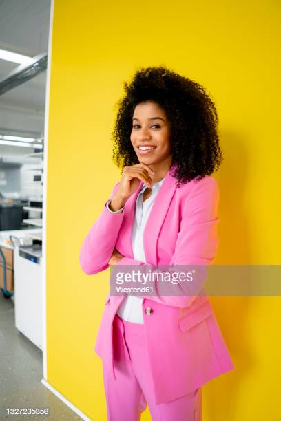 smiling businesswoman with hand on chin standing in front of yellow wall - three quarter length stock pictures, royalty-free photos & images