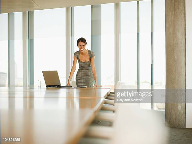 Smiling businesswoman with laptop in empty conference room