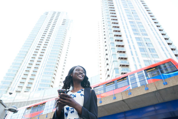 Smiling businesswoman with mobile phone against metro train and skyscrapers