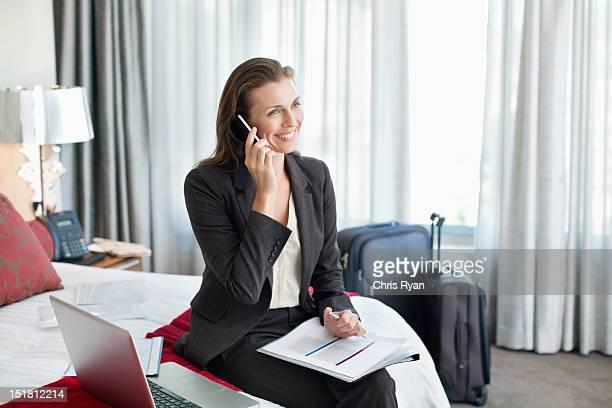 Lächelnd Geschäftsfrau mit Papierkram sprechen auf Handy in ho