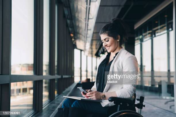 smiling businesswoman with physical disability using smart phone in office corridor - minder validen stockfoto's en -beelden
