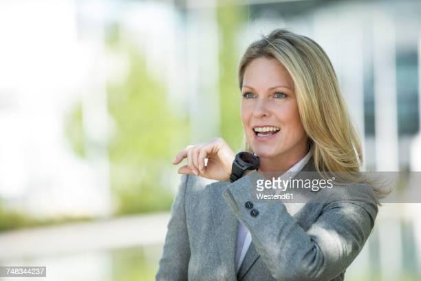 smiling businesswoman with smartwatch outdoors - finanzwirtschaft und industrie stock-fotos und bilder