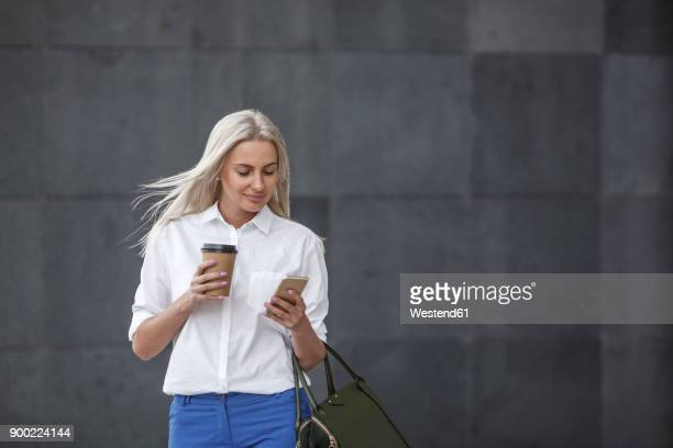 Smiling businesswoman with takeaway coffee and cell phone on the move