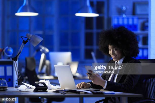 Smiling businesswoman working late and using smart phone