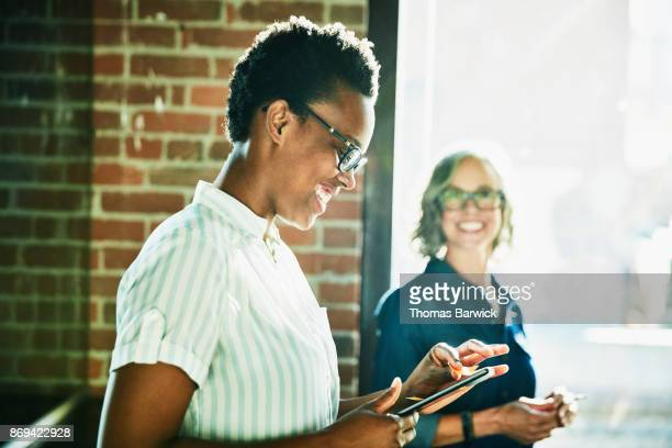 Smiling businesswoman working on digital tablet during meeting with coworkers in office conference room