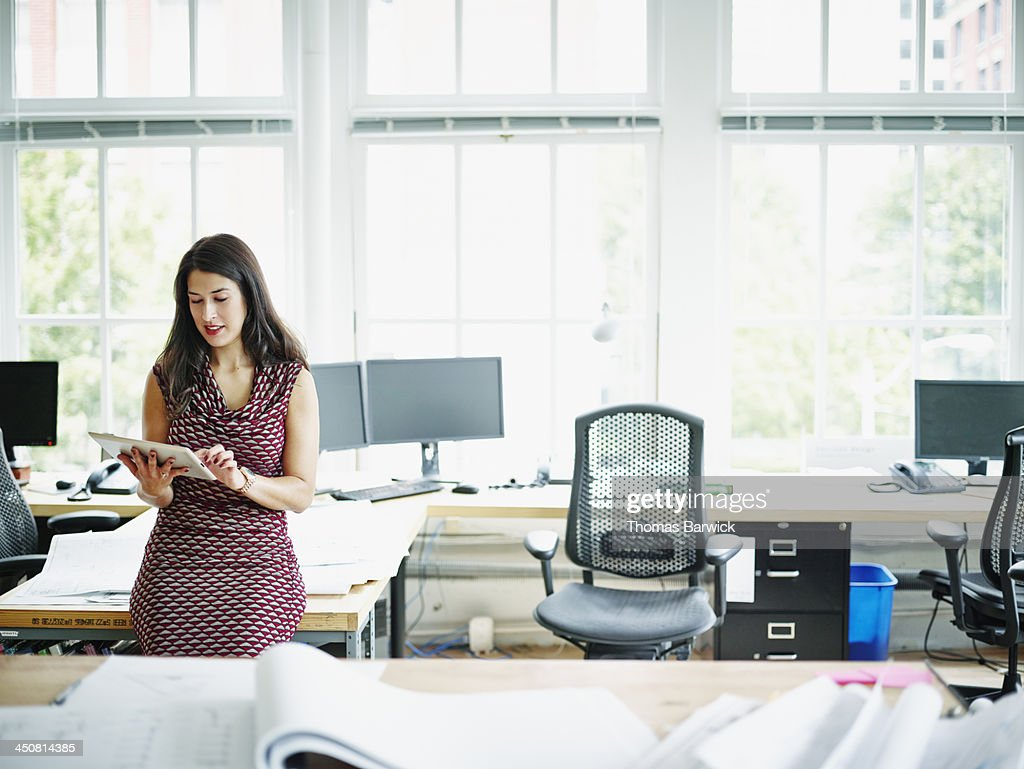 Smiling businesswoman working on digital tablet : Stock Photo