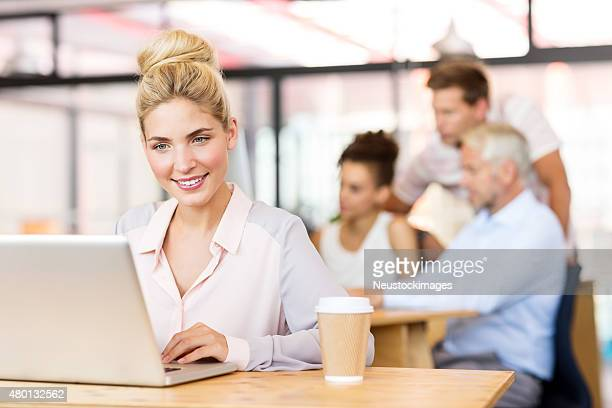 Smiling Businesswoman Working On Laptop At Office Desk