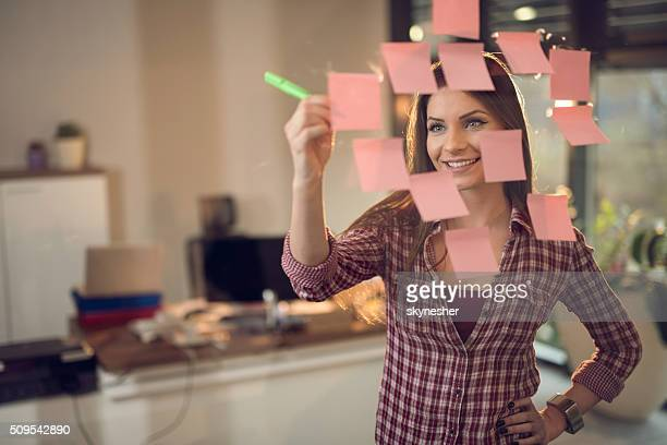 Smiling businesswoman writing adhesive notes on glass wall.
