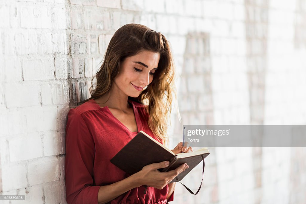 Smiling businesswoman writing in diary at office : Stock Photo