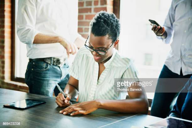Smiling businesswoman writing notes during meeting in office conference room