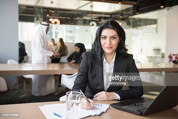 Smiling businesswoman writing on document