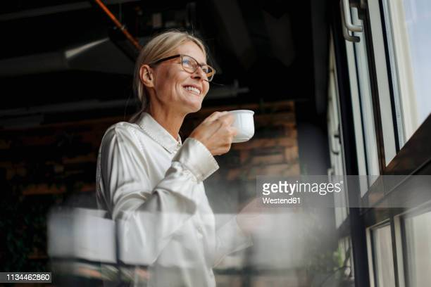 smiling businesswomanholding cup of coffee looking out of window - messa a fuoco differenziale foto e immagini stock