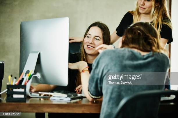 smiling businesswomen having project meeting in design office - doing a favor stock pictures, royalty-free photos & images
