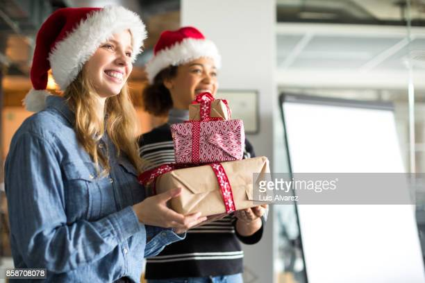 Smiling businesswomen holding Christmas gifts in office