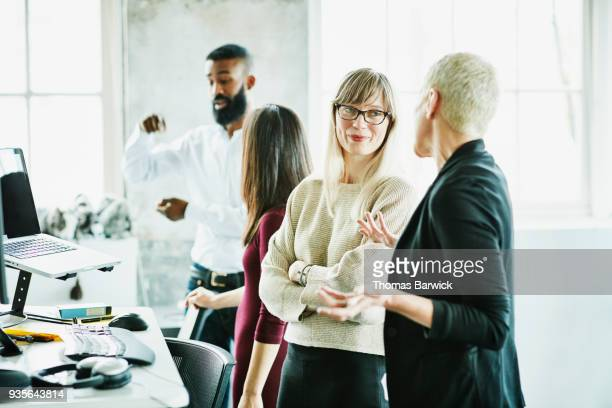 smiling businesswomen in discussion at workstation in high tech start up - non verbal communication stock photos and pictures