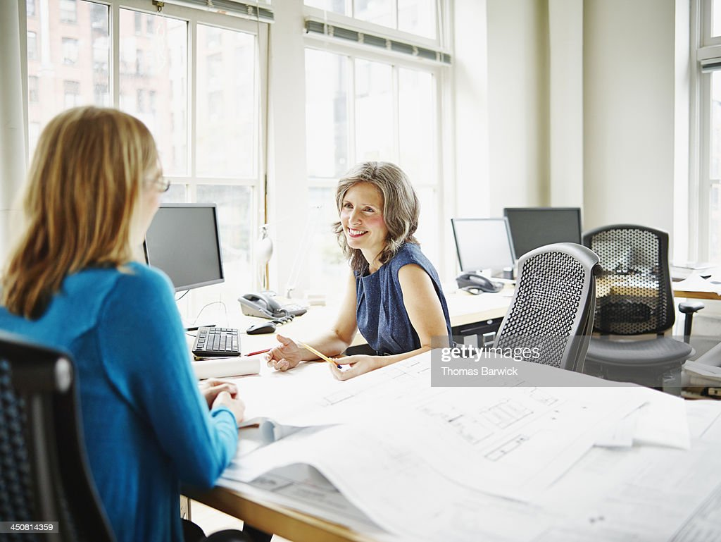 Smiling businesswomen in discussion in office : Stock Photo