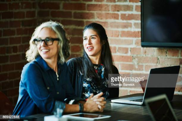 Smiling businesswomen in discussion with clients during meeting in office conference room