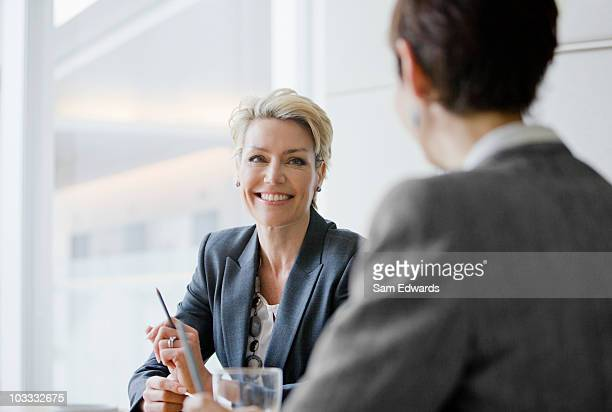 smiling businesswomen in meeting - zakenbijeenkomst stockfoto's en -beelden