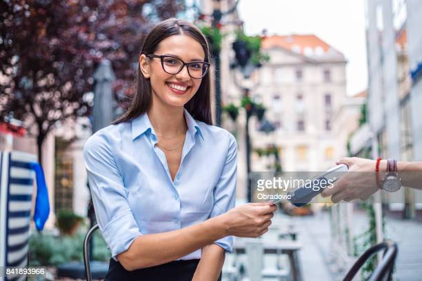 Smiling bussines woman paying for coffee by credit card