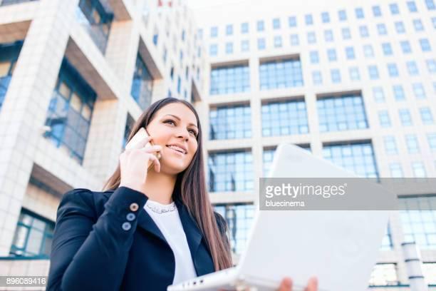 Bussineswoman 通りに電話で話している笑みを浮かべてください。