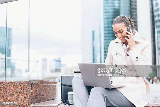 Smiling bussineswoman using laptop on street