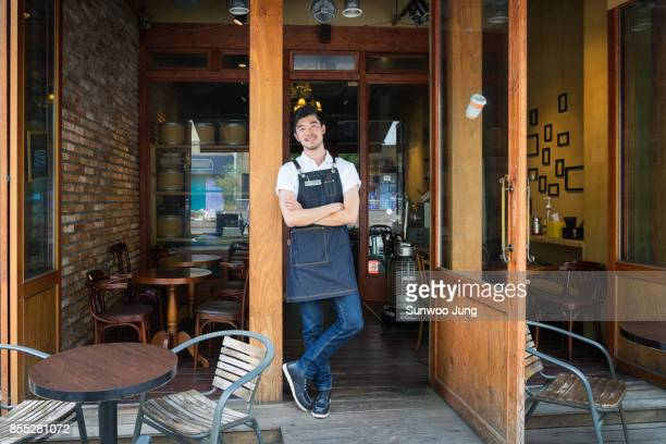 smiling cafe owner standing in front of store - legs crossed at ankle stock pictures, royalty-free photos & images