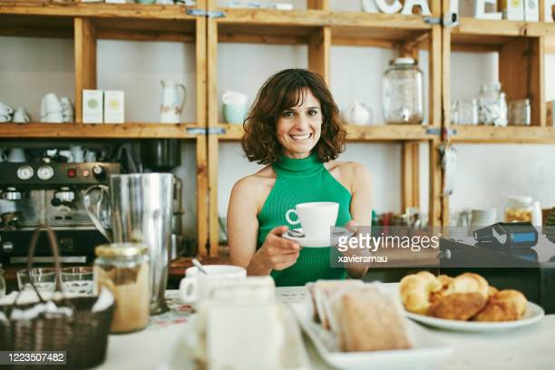 smiling cafe worker holding cup of coffee behind counter - mid length hair stock pictures, royalty-free photos & images