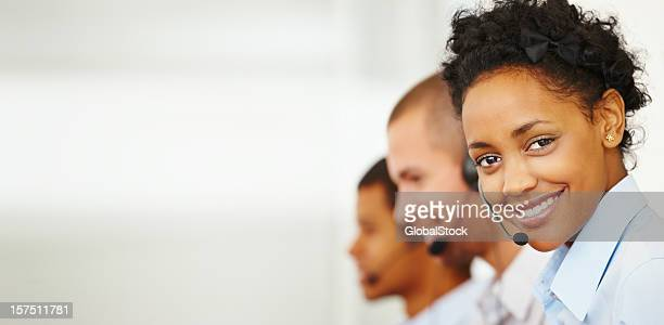 Smiling call center employee with two colleagues behind her