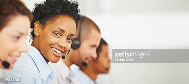 Smiling call center employee working with her colleagues