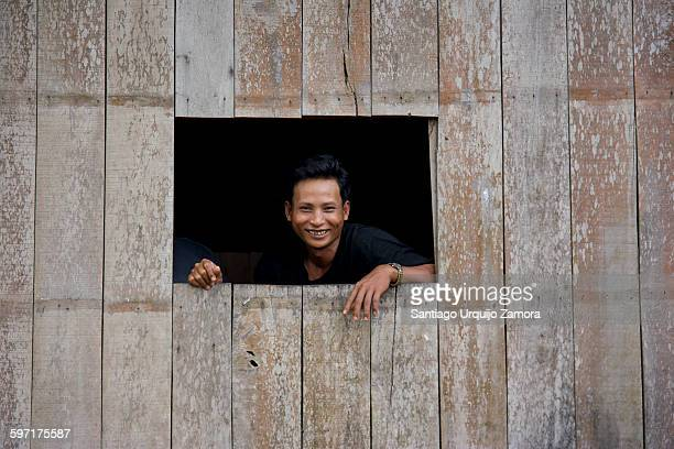 Smiling Cambodian man on a window at Kratie, Kratie Province, Cambodia