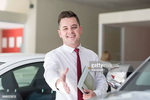 Smiling car dealer in showroom reaching out his hand
